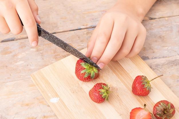 Teenager cutting strawberries on kitchen board to make smoothie balls, metal knife