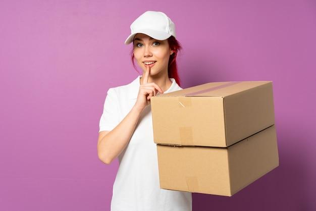 Девочка доставки подростка, изолированные на фиолетовом фоне, показывая знак жеста молчания, положив палец в рот