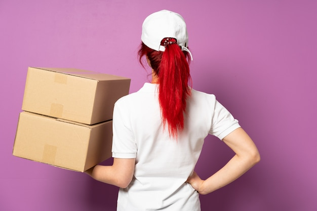 Teenager delivery girl isolated on purple background in back position