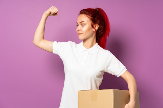 Teenager delivery girl isolated on purple background doing strong gesture