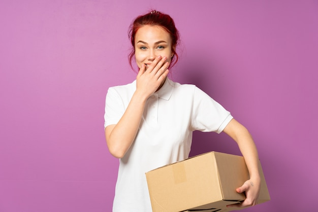 Teenager delivery girl isolated on purple background happy and smiling covering mouth with hand