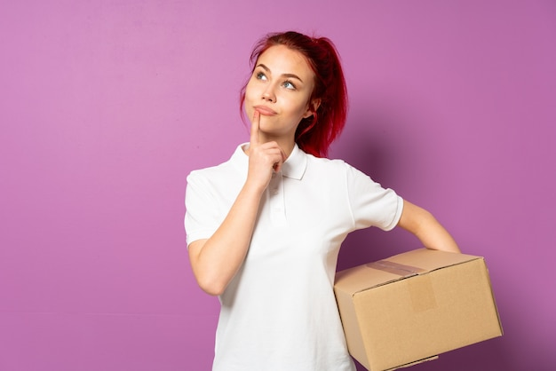 Teenager delivery girl isolated on purple background having doubts while looking up