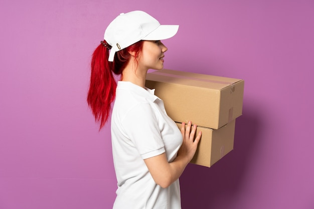Teenager delivery girl isolated on purple background in lateral position