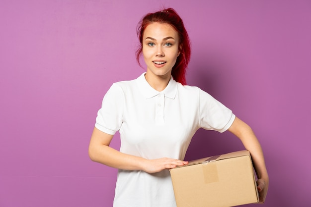 Teenager delivery girl isolated on purple background laughing