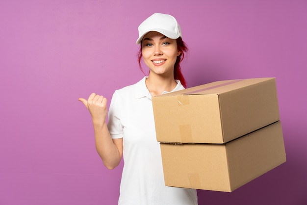 Teenager delivery girl isolated on purple background pointing to the side to present a product