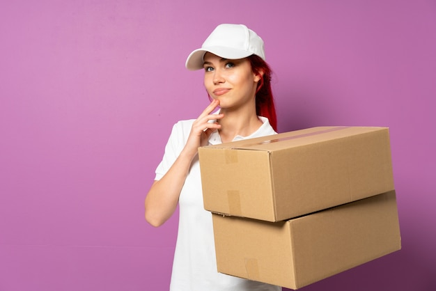 Teenager delivery girl isolated on purple background scheming something