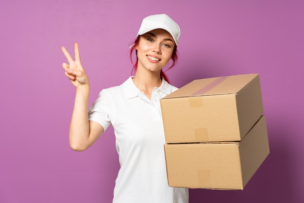 Teenager delivery girl isolated on purple background showing victory sign with both hands