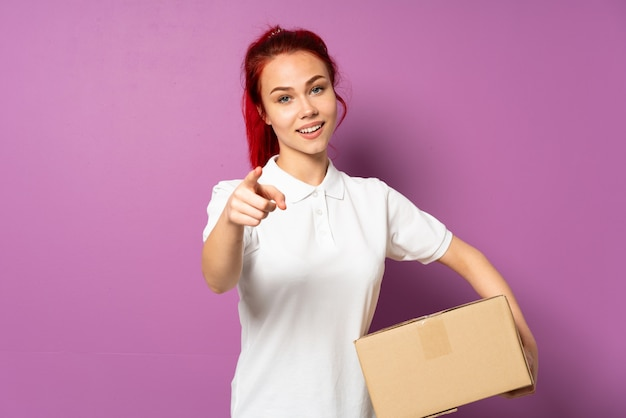 Teenager delivery girl isolated on purple background surprised and pointing front