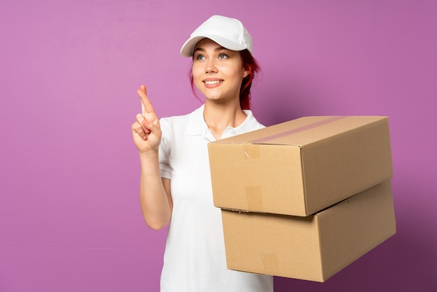 Teenager delivery girl isolated on purple background with fingers crossing and wishing the best