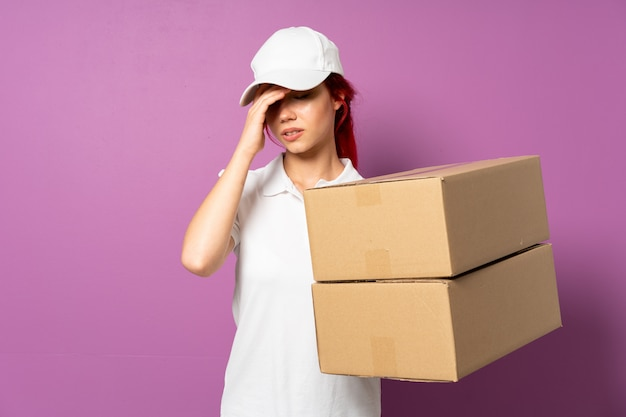 Teenager delivery girl isolated on purple background with headache