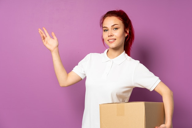Teenager delivery girl isolated on purple wall extending hands to the side for inviting to come