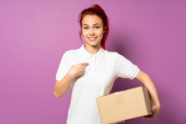 Teenager delivery girl isolated on purple wall with surprise facial expression
