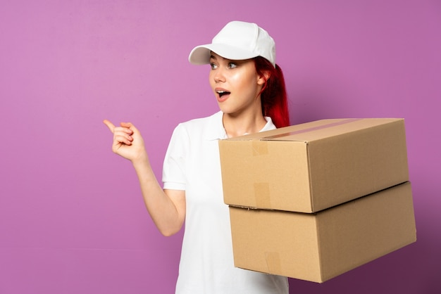 Teenager delivery woman isolated on purple wall intending to realizes the solution while lifting a finger up