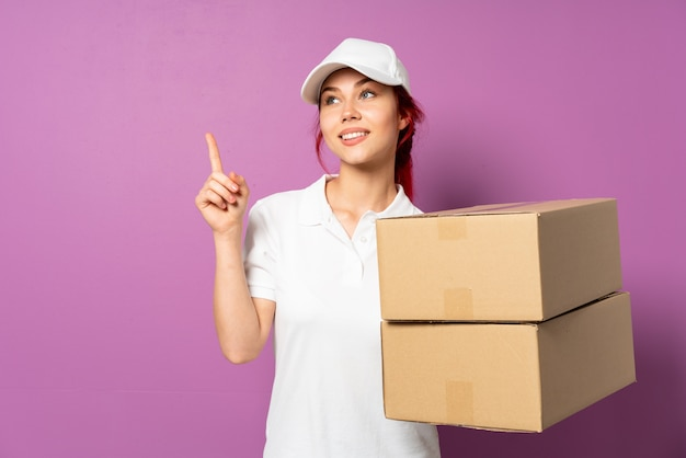 Teenager delivery woman isolated on purple wall pointing up a great idea