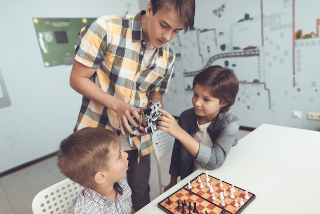 Teenager demonstrating robot to two sitting boys.