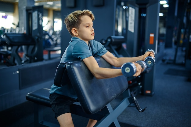 Teenager doing exercise with dumbbells in gym, side view. youngster on training in sport club, healthcare and healthy lifestyle, schoolboy on workout, sportive youth