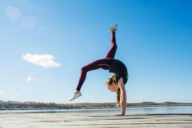 Teenager doing gymnastic on pier