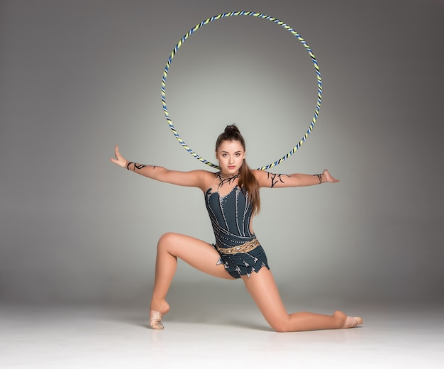 Teenager doing gymnastics exercises with colorful hoop on a gray background