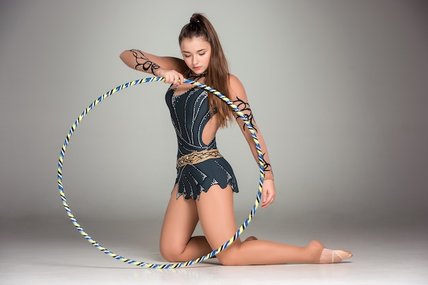 Teenager doing gymnastics exercises with colorful hoop on gray
