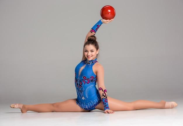 Подросток делает гимнастические упражнения с красным гимнастическим мячом на сером фоне