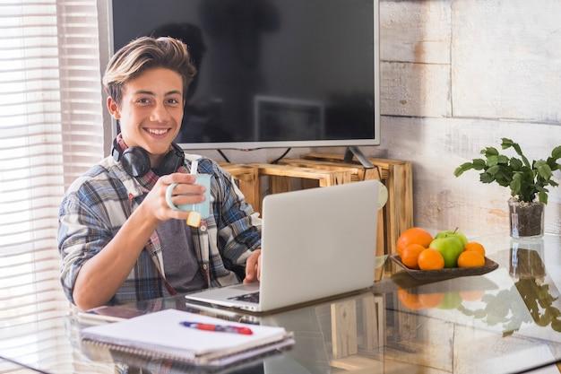 ノートパソコンと自宅で宿題をしているティーンエイジャー-屋内と勉強の概念-カメラを見て笑っている男