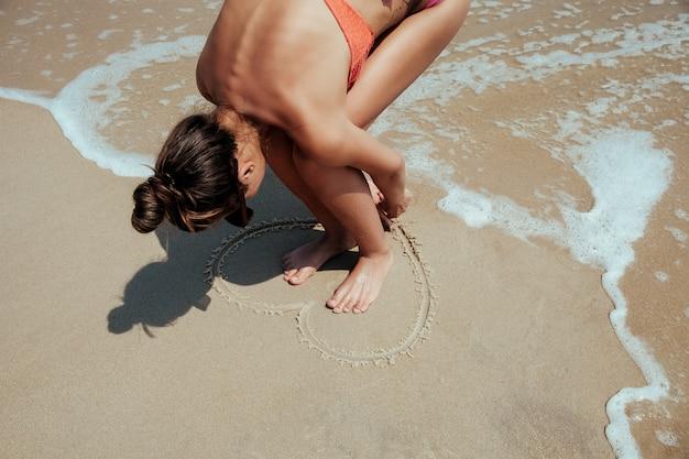 Подросток рисунок сердце на песке.