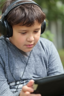 Teenager in earphones outdoor listening to music or watching video on tablet pc