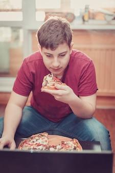Подросток ест пиццу, сидя за ноутбуком.