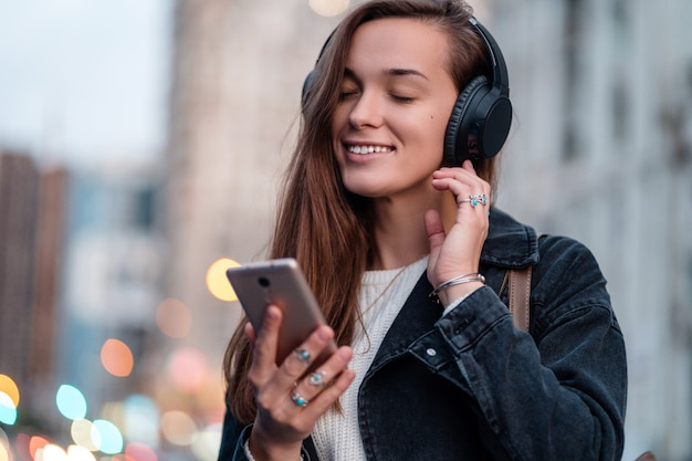 Teenager enjoys and listens to music in black wireless headphones while walking around the city