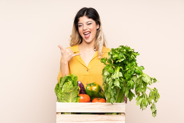 Teenager farmer girl with freshly picked vegetables in a box on beige wall making phone gesture
