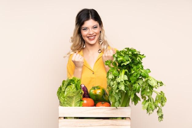 勝利を祝ってベージュの壁に分離されたボックスで摘みたての野菜と10代の農家の少女