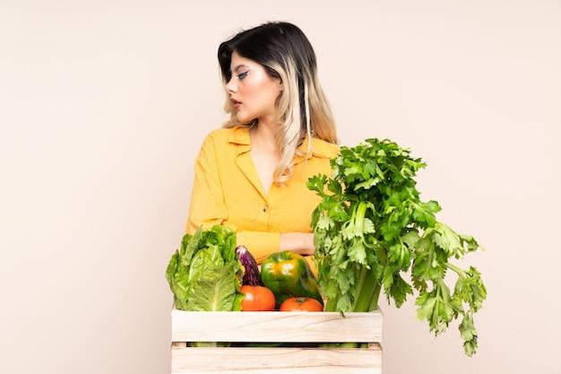 側を見てベージュの壁に分離されたボックスで摘みたての野菜と10代の農家の少女