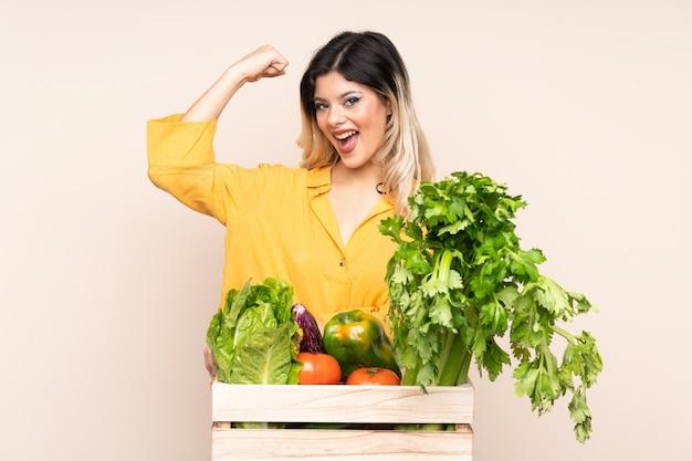 強いジェスチャーを作るベージュの壁に分離されたボックスで摘みたて野菜と10代の農家の少女