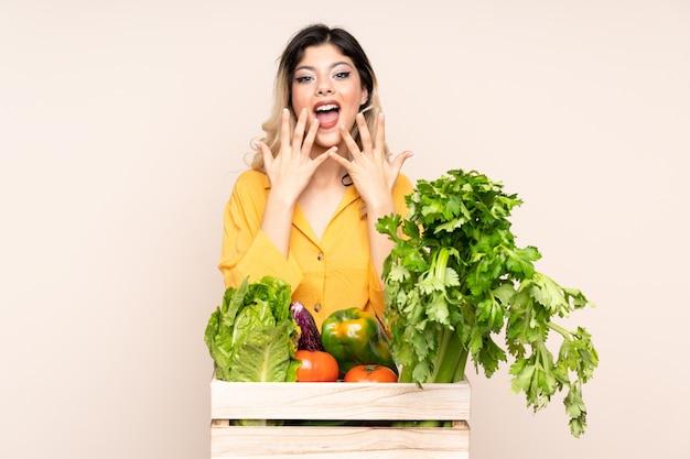 Девушка-подросток-фермер со свежесобранными овощами в коробке