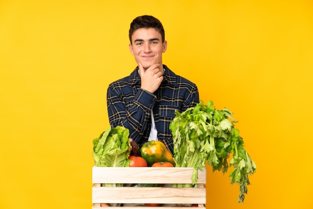 Teenager farmer man with freshly picked vegetables in a box laughing