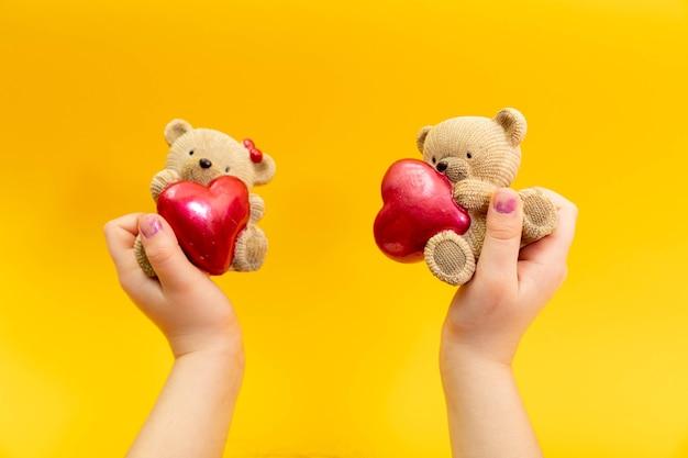 십 대 여성의 손을 노란색 배경, 평면도에 붉은 마음으로 작은 장난감 곰을 잡아. 발렌타인 데이 개념.