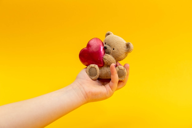 Teenager female hand hold a small toy teddy bear with red heart on a yellow background, top view. valentine day concept.