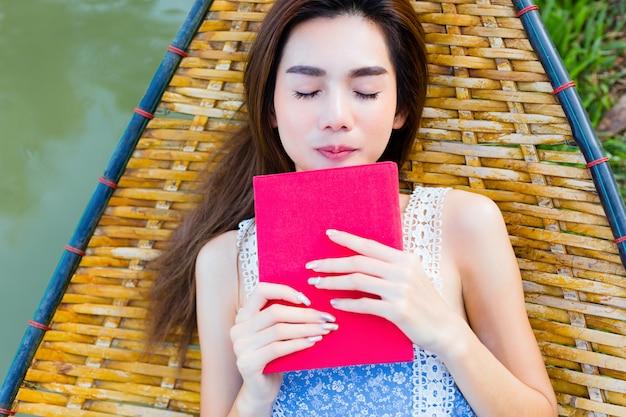 Девушка-подросток лежит на бамбуковом гамаке и читает книгу
