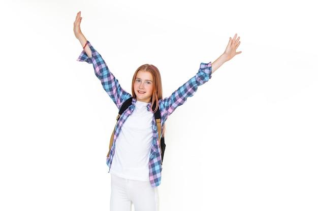 십 대 소녀 11 세 모범생 배낭과 흰색 배경에 카메라를 보고 그녀의 손을 높이 들고 웃 고. 격자 무늬 셔츠를 입고. 복사 공간