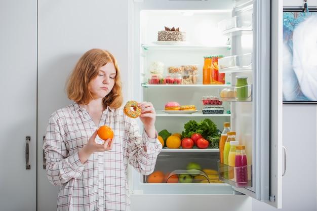 Девушка-подросток в холодильнике с едой