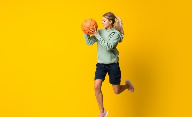 Teenager girl basketball ball jumping over isolated yellow wall