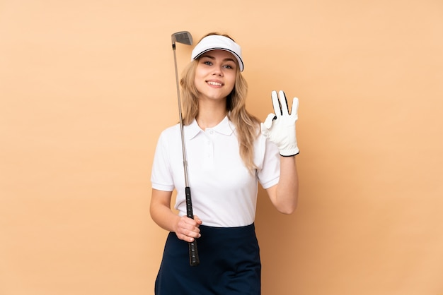 Teenager girl on beige wall playing golf making ok sign