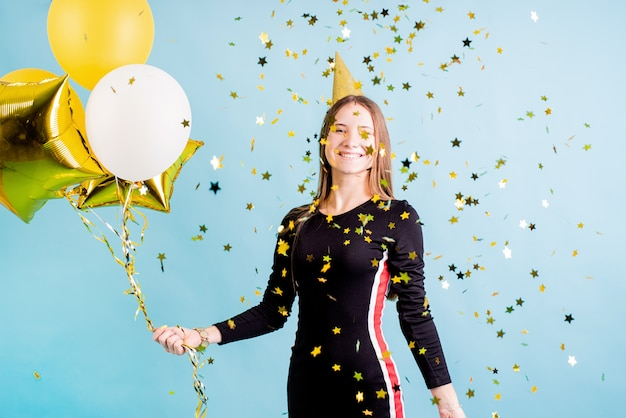 Девушка-подросток дует конфетти на синем фоне с воздушными шарами