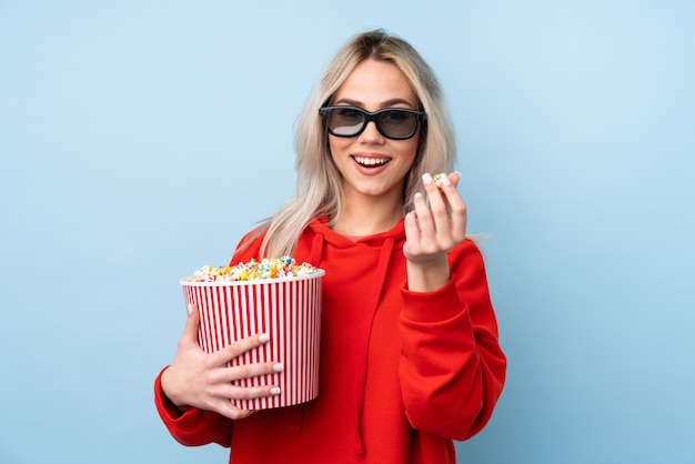 Teenager girl over blue wall with 3d glasses and holding a big bucket of popcorns