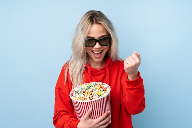 Teenager girl over blue with 3d glasses and holding a big bucket of popcorns