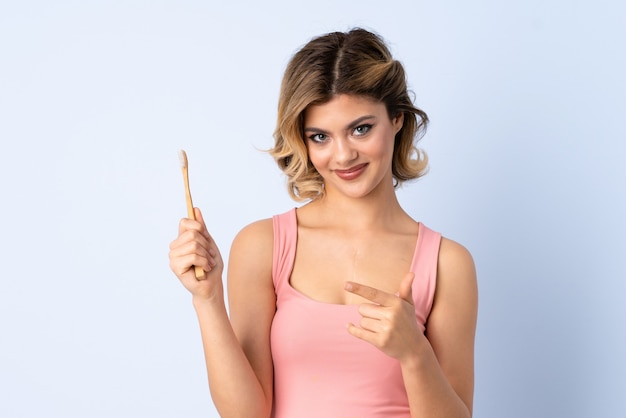 Teenager girl brushing her teeth isolated on blue pointing to the side to present a product