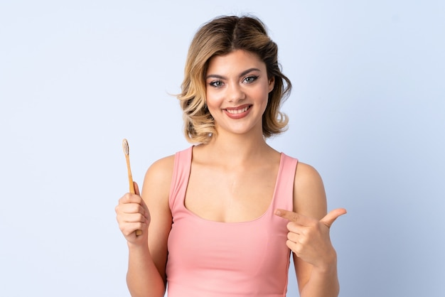 Teenager girl brushing her teeth isolated on blue with surprise facial expression