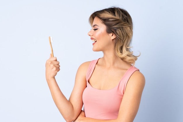 Teenager girl brushing her teeth with happy expression