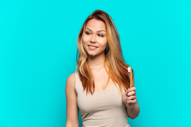 Teenager girl brushing teeth over isolated blue background looking to the side and smiling