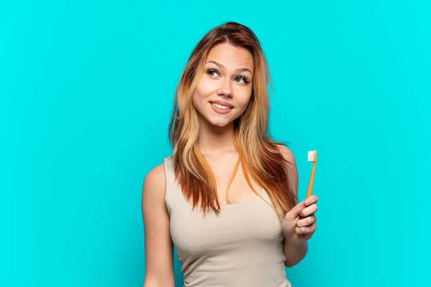 Teenager girl brushing teeth over isolated blue background thinking an idea while looking up